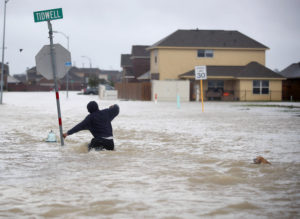 HOUSTON, TX - AUGUST 28: A person walks through a flooded street with a dog after the area was inundated with flooding from Hurricane Harvey on August 28, 2017 in Houston, Texas. Harvey, which made landfall north of Corpus Christi late Friday evening, is expected to dump upwards to 40 inches of rain in Texas over the next couple of days. (Photo by Joe Raedle/Getty Images)